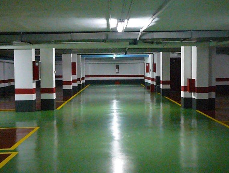 Garaje blanco con zócalo negro y rojo, suelo verde, rojo y amarillo