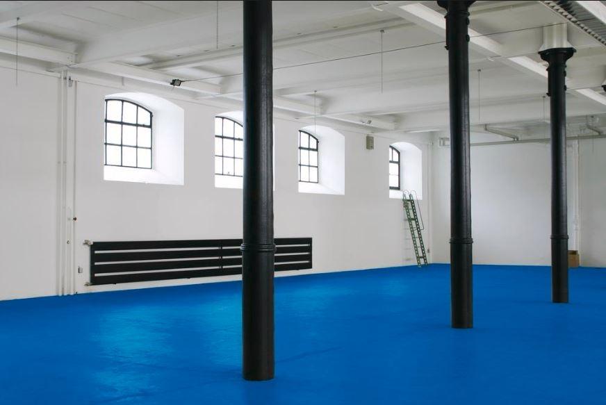 Nave suelo azul soportes en negro y paredes blancas