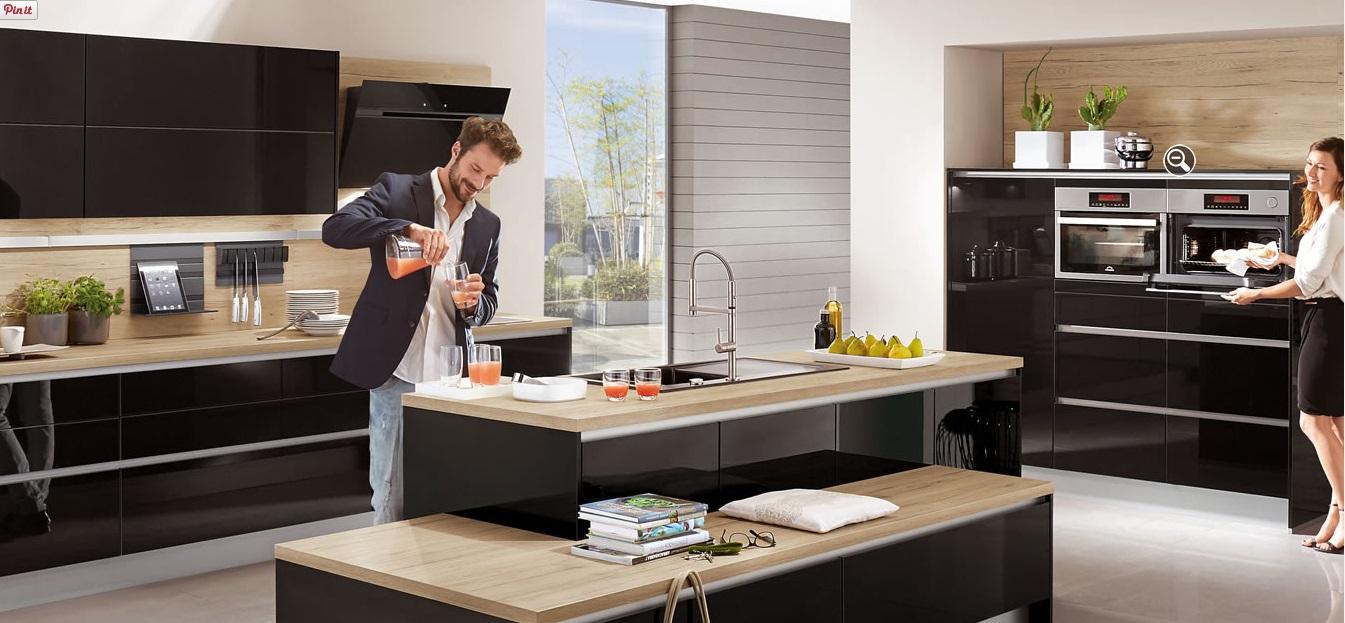 Reformas de cocinas. Pareja de matrimonio sirviéndose un zumo en la cocina moderna con muebles negros y diseño con isla
