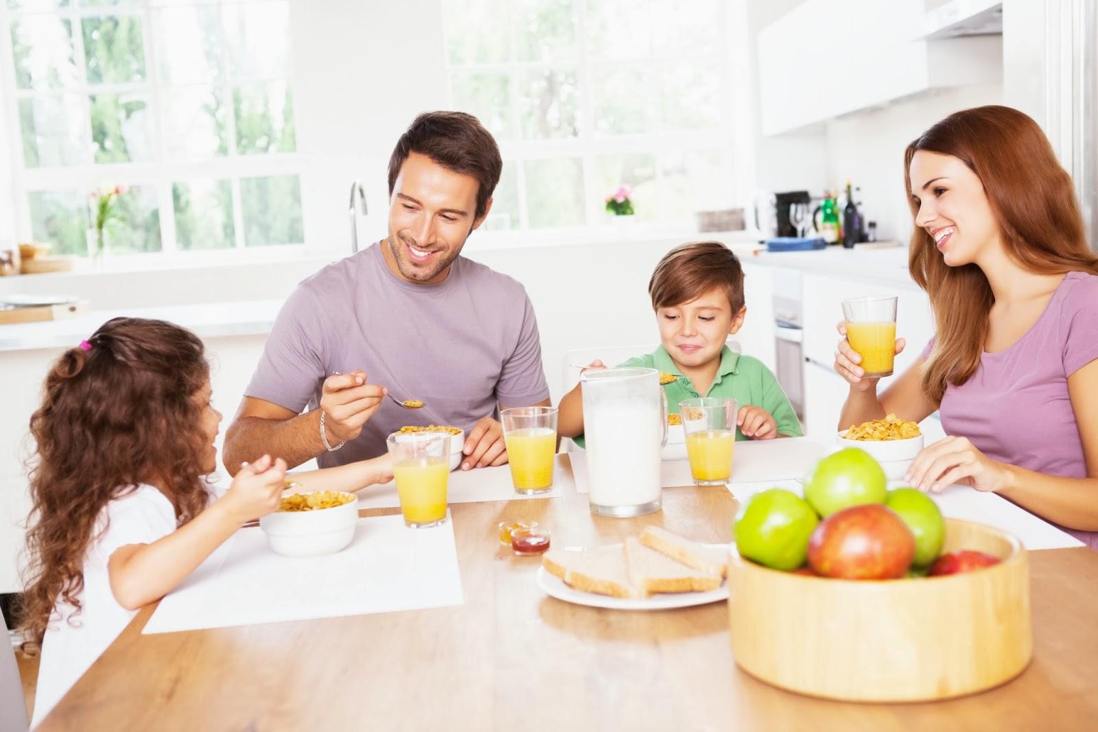 Arcolínea: Reformas de cocinas. Pareja con niño y niña desayunando felices en la cocina.